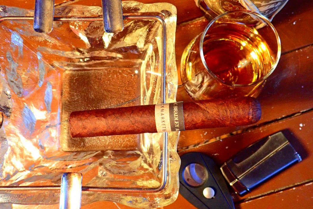 Zigarre im Aschenbecher mit Rumgals und Flasche