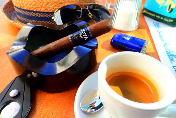 Zigarre im Aschenbecher mit diversen Utensilien