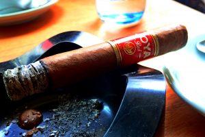Zigarre mit roter Banderole in Aschenbecher