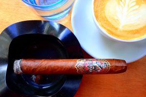 Zigarre im Aschenbecher neben Kaffe und Wasserglas