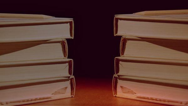 Zwei Bücherstapel vor rotem Hintergrund