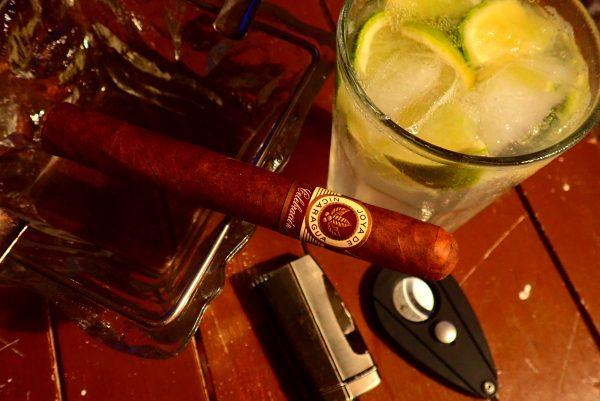 Zigarre im Aschenbecher und Cocktail im Hintergrund