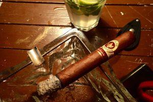 Zigarre in Aschenbecher vor Mojito