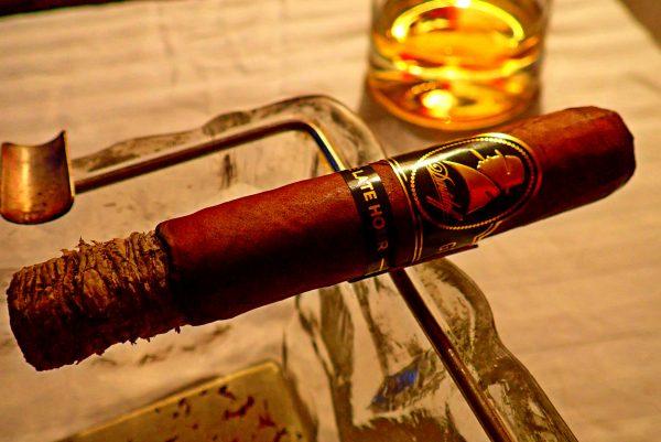 Zigarre in Aschenbecher vor Whiskyglas