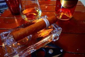 Zigarre in Aschenbecher vor Weinbrand