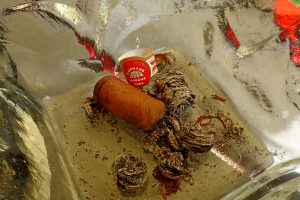 Zigarrenasche samt Zigarre in Aschenbecher